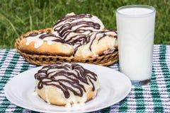 Homemade cinnabons cinnamon buns with cream cheese glaze and chocolate icing and  glass of milk Stock Photos