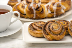 Homemade cinnamon buns and a cup of tea on the wooden background. Stock Image