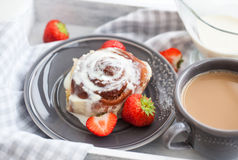 Homemade cinnamon rolls. Homemade cinnamon roll pastry with icing and strawberry Stock Photos