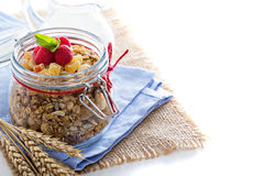 Homemade citrus granola in a glass jar on white Stock Images