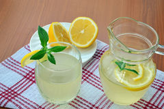 Homemade citrus lemonade. Refreshing summer lemonade with lemon in glass and pitcher stock photography