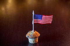 Cupcake and flag of the United States. Homemade classic cupcake and flag of the United States with fairy lights in bokeh royalty free stock photos