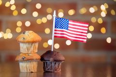 Cupcakes and flag of the United States. Homemade classic cupcakes and flag of the United States with fairy lights in bokeh royalty free stock images