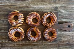 Homemade classic donuts with chocolate and coconut flakes on a dark wooden background. The top view, flat lay stock photography