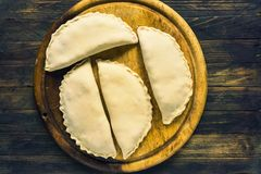 Homemade closed pies with stuffing. On a wooden board Stock Image