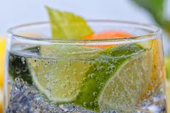Homemade cocktail with citrus fruits in glass cup with transparent drink and ices royalty free stock images