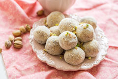 Homemade coconut balls decorated with little pink flowers Royalty Free Stock Photos