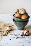 Homemade coconut macaroons with dripped dark chocolate on bowl Stock Photo