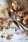 Homemade coconut macaroons with dripped dark chocolate and cocoa powder on tray with chocolate backdrop Stock Photos