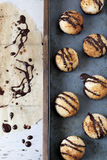 Homemade coconut macaroons with dripped dark chocolate on greaseproof paper Stock Image