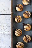 Homemade coconut macaroons with dripped dark chocolate on vintage blue tray Stock Image