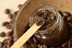 Homemade coffee scrub in a glass jar over coconut shell and coffee beans royalty free stock images