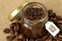 Homemade coffee scrub in a glass jar over jute sack and coffee b royalty free stock images