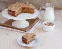 Homemade coffee and walnut cake on a stand with a slice Stock Image