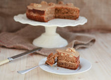 Homemade coffee and walnut cake on a stand with a slice Stock Photos