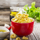 Homemade comfort food: Italian tortellini in a red ceramic bowl on a rustic wooden background with olive oil, black Stock Photo