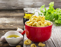 Homemade comfort food: Italian tortellini in a red ceramic bowl on a rustic wooden background with olive oil, black Stock Image