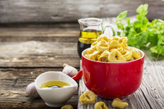 Homemade comfort food: Italian tortellini in a red ceramic bowl on a rustic wooden background with olive oil, black Stock Photography