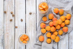 Homemade conserve of apricot pieces in glass jars. Slices of fresh apricot in glass jars and napkin on a wooden table royalty free stock photo