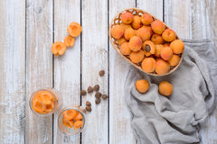 Homemade conserve from pieces of apricots. Slices of apricots in a glass jar, basket apricot and napkin on vintage wooden table royalty free stock image