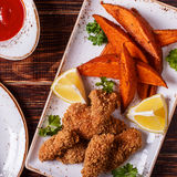Homemade cooked nuggets and sweet potatoes. Stock Images