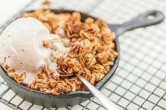 Homemade cooked rhubarb and apple crumble with oatmeal and vanil. La ice cream in the iron pans stock images