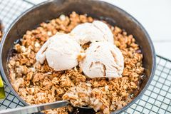 Homemade cooked rhubarb and apple crumble with oatmeal and vanilla ice cream stock images
