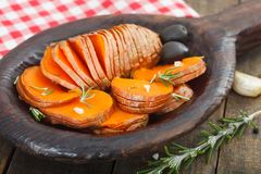 Homemade Cooked Sweet Potato. With spices and herbs in wooden plate Stock Image