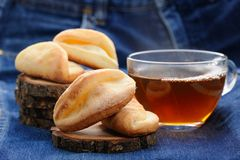 Homemade cookies and black tea on wooden stands on deep blue clo Stock Photos