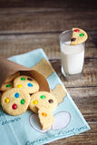 Homemade cookies with color candies in cornet. On wood background and a glass of milk Stock Images