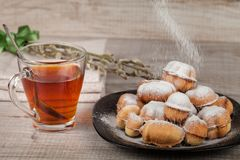 Homemade cookies with condensed milk stuffed with nuts. Covered with powdered sugar and a cup of tea royalty free stock photo