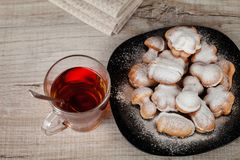 Homemade cookies with condensed milk stuffed with nuts. Covered with powdered sugar and a cup of tea royalty free stock photos