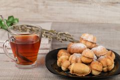 Homemade cookies with condensed milk stuffed with nuts. Covered with powdered sugar and a cup of tea royalty free stock image