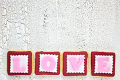 Homemade cookies creating word LOVE on white old wooden background, top view stock image
