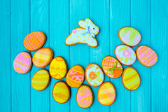 Homemade cookies with icing in the shape of an egg for Easter. Delicious Easter cookies on a blue background. Colored glaze. Royalty Free Stock Image
