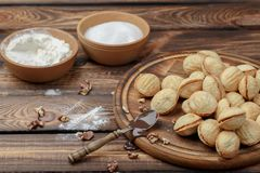 Homemade cookies, nuts with condensed milk on wooden background. rural style. A spoon with condensed milk royalty free stock images