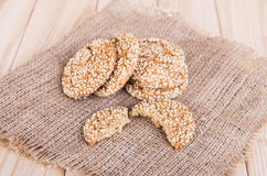 Homemade cookies with sesame seeds,  on wooden  table. On sackcloth background Royalty Free Stock Photos