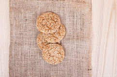 Homemade cookies with sesame seeds,  on wooden  table. On sackcloth background royalty free stock image