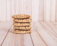 Homemade cookies with sesame seeds, on wooden table. On sackcloth background royalty free stock images