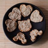 Homemade cookies in the shape of a heart and a cat, oatmeal pastries on a black round plate on a beige background. Homemade cookies in the shape of a heart and a stock photography
