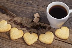 Homemade cookies in the shape of a heart and coffee. Homemade shortbread cookies in the shape of a heart and cup of coffee on old wooden background stock photography