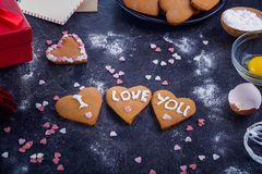 Homemade cookies in shape of heart with I Love you words as gift for lover on Valentine`s day. Dark stone background with ingredi Stock Photography