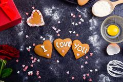 Homemade cookies in shape of heart with I Love you words as gift for lover on Valentine`s day. Dark stone background with ingredi. Ents, flower and decor. Love Stock Photo