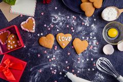 Homemade cookies in shape of heart with I Love you words as gift for lover on Valentine`s day. Dark stone background with ingredi. Ents, flower and decor. Love Stock Photography