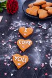Homemade cookies in shape of heart with I Love you words as gift for lover on Valentine`s day. Dark stone background with ingredi Stock Images