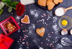 Homemade cookies in shape of heart with Love word as gift for lover on Valentine`s day. Dark stone background with ingredients, f. Homemade cookies in shape of Royalty Free Stock Photo