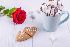 Homemade cookies in shape of heart with Love you lettering on the white wooden table with rose flower and cup of cacao with marshm Stock Photo