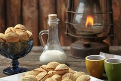 Homemade cookies shaped nuts with cream boiled condensed milk on wooden table. Rustic style. Coffee and milk. fire in a lamp royalty free stock image