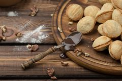 Homemade cookies shaped nuts with cream boiled condensed milk on wooden table. Rustic style. spoon with condensed milk. Scattered cleared nuts stock images