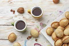 Homemade cookies shaped nuts with cream boiled condensed milk on wooden table. Rustic style. Two cups of coffee. Top view royalty free stock photography